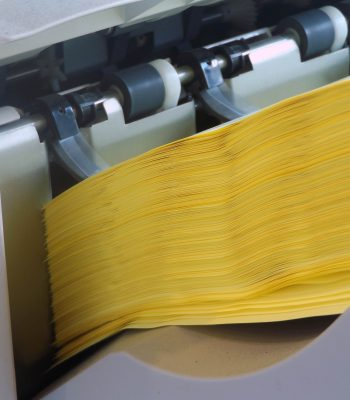 A yellow stack of 80 gsm paper that has finished printing, neatly stacked at the end of a job by the Xerox Docucolour 252 printer