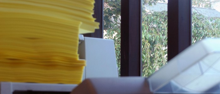 A stack of yellow paper on top of the printer, with a view out the window of Pendred Printing into Cobble Yard