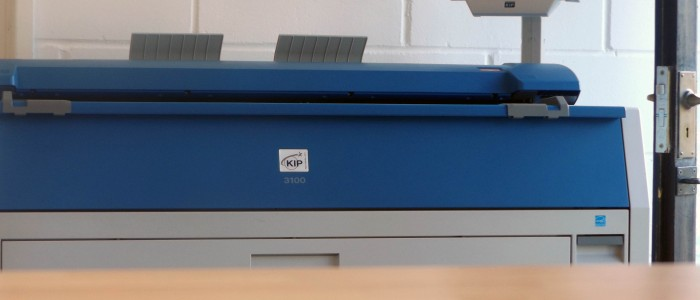 A view from the desk showing the KIP 3100 large format printer