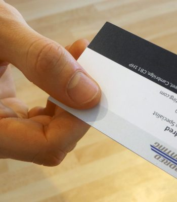 A hand holding a business card and passing it to the camera, business card shows Pendred Printing logo